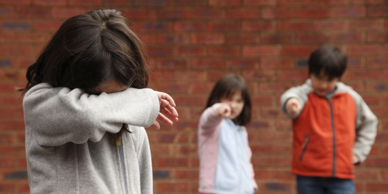 Image of child with face covered and being bullied.