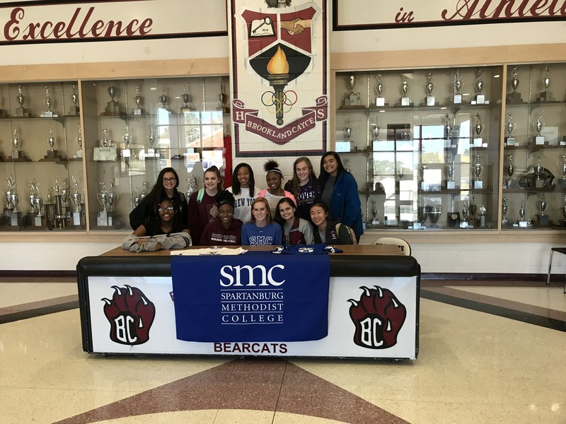 Savannah Ducote signs her letter of intent, surrounded by fellow BC volleyball players.