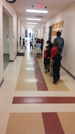 Elementary school students practicing walking in the halls