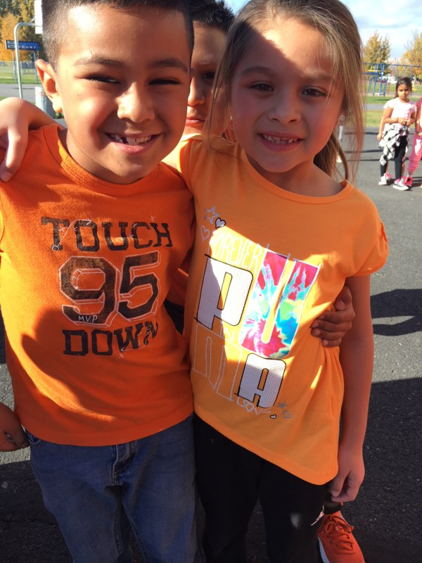 A boy and a girl wearing orange shirts in support of Unity Day.