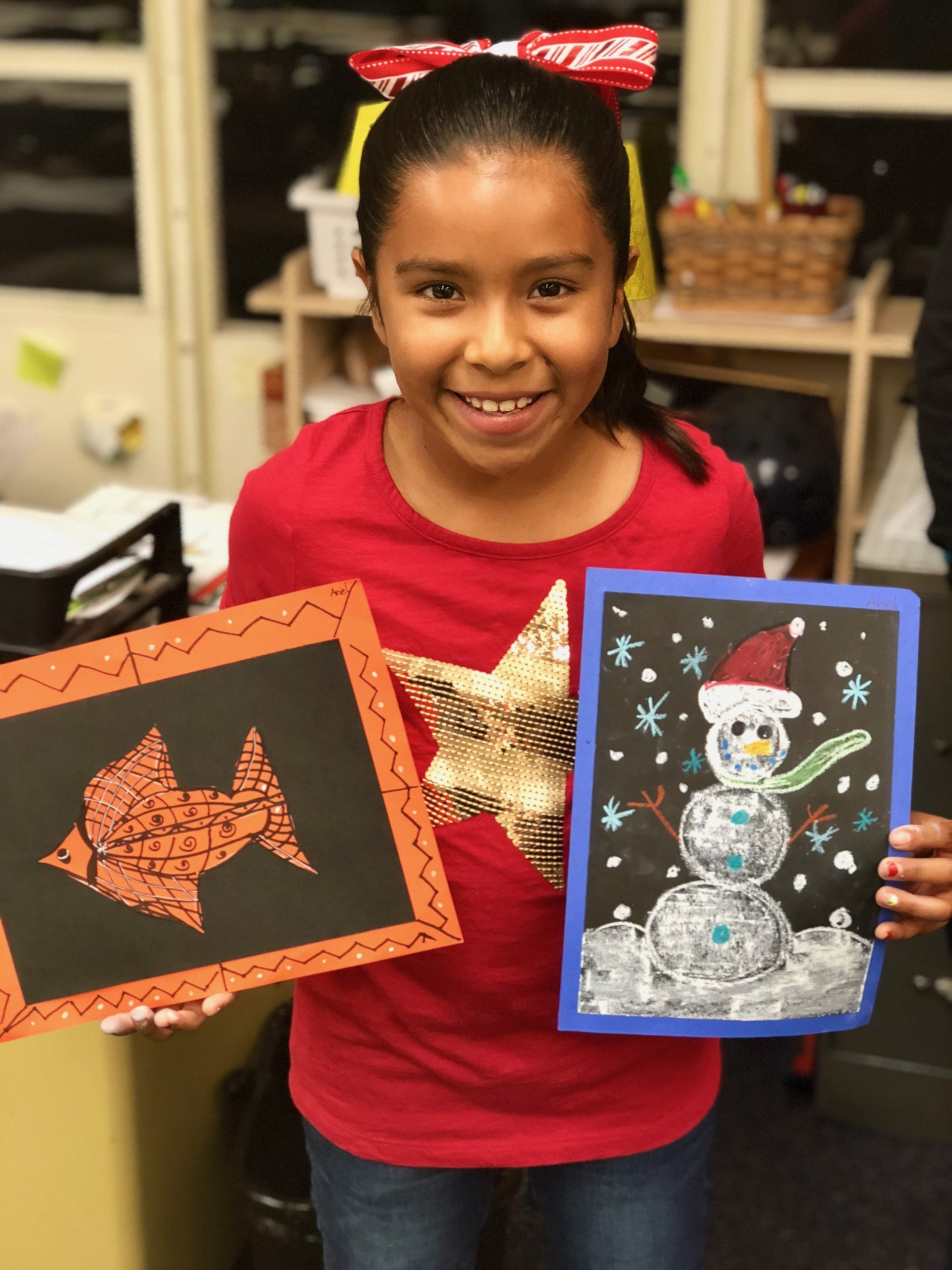 A girl showing her drawings of a fish and a snowman.