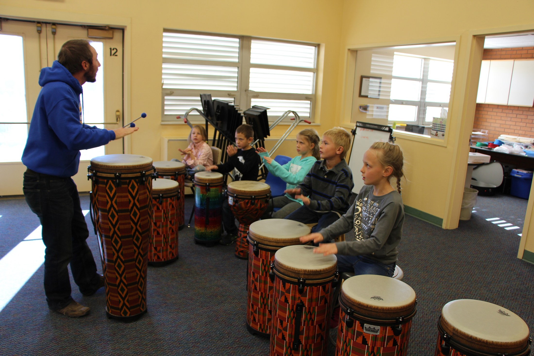 Students play drums in music class.