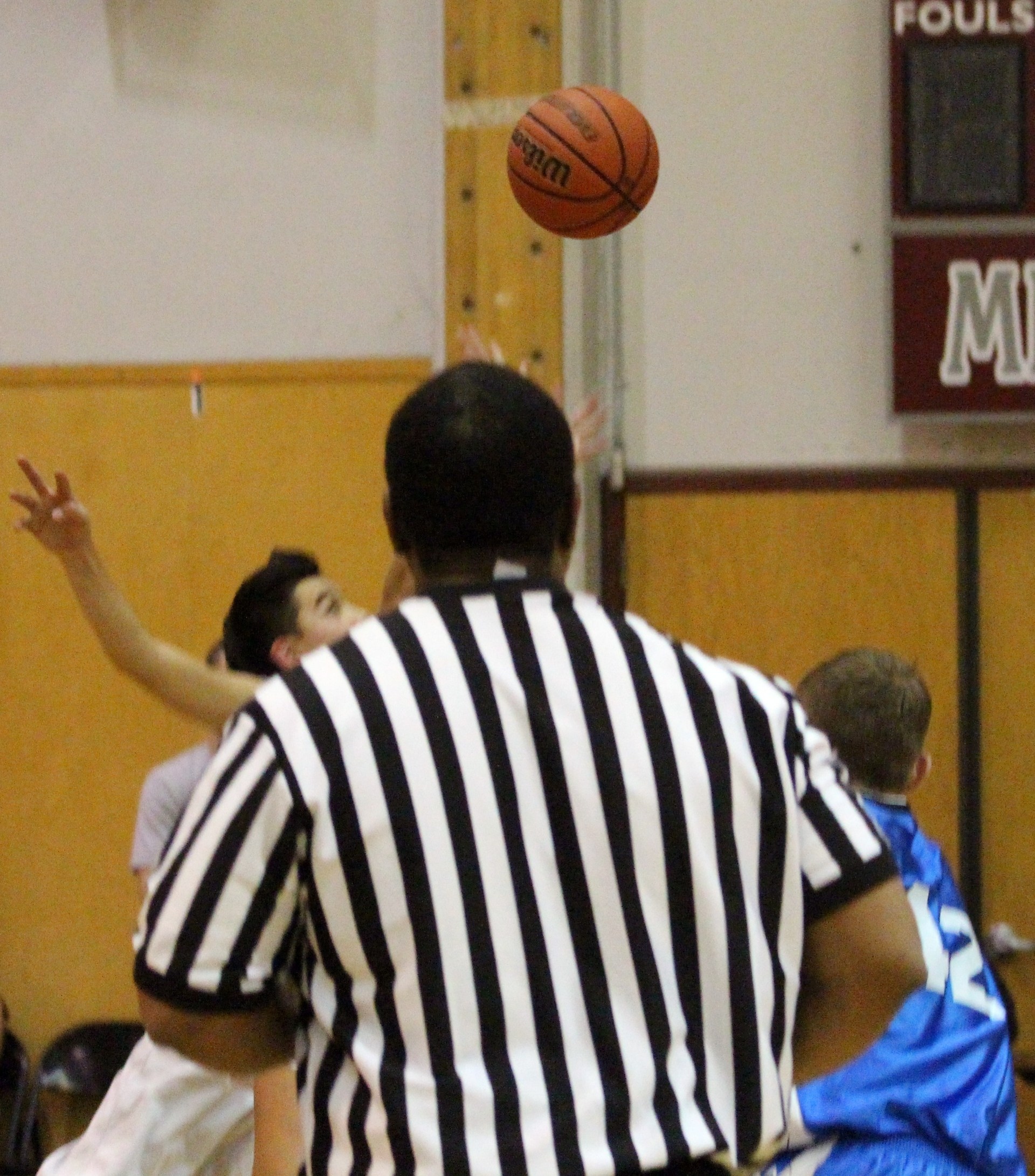Picture of a basketball surrounded by players and referee.
