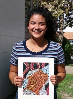 Rebecca holding a print sample of her painting