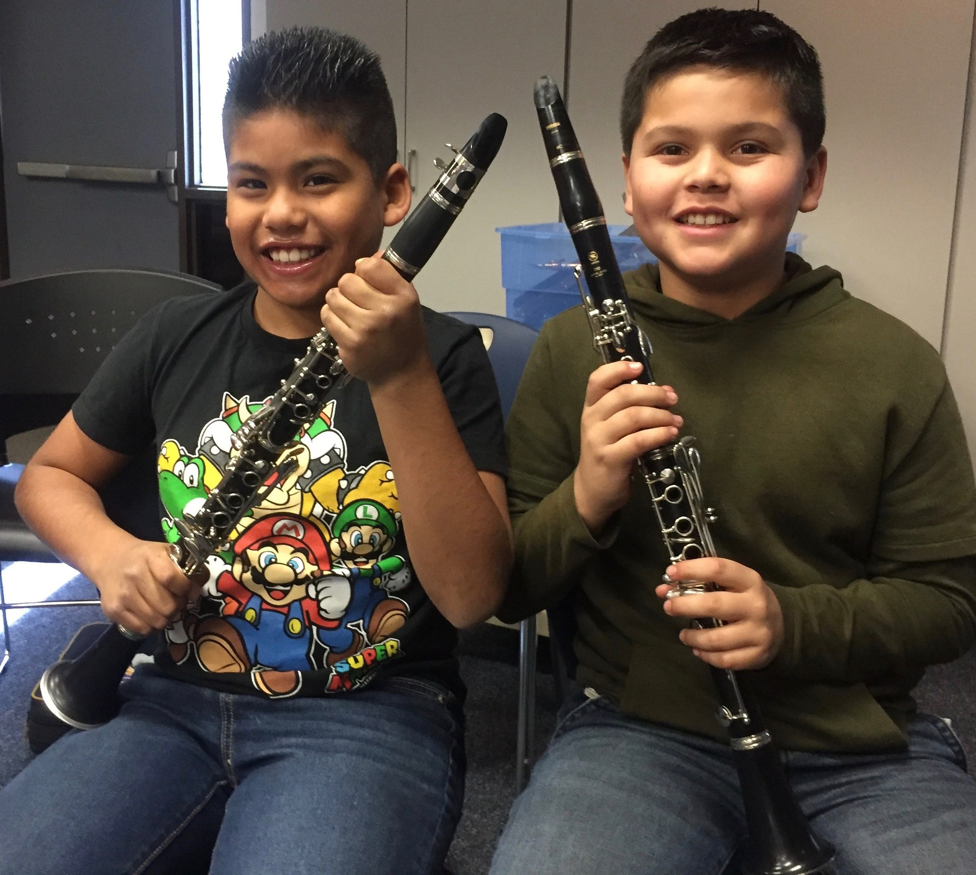 Two boys showing their clarinets.