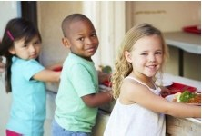 Diverse children standing in line getting tray lunches