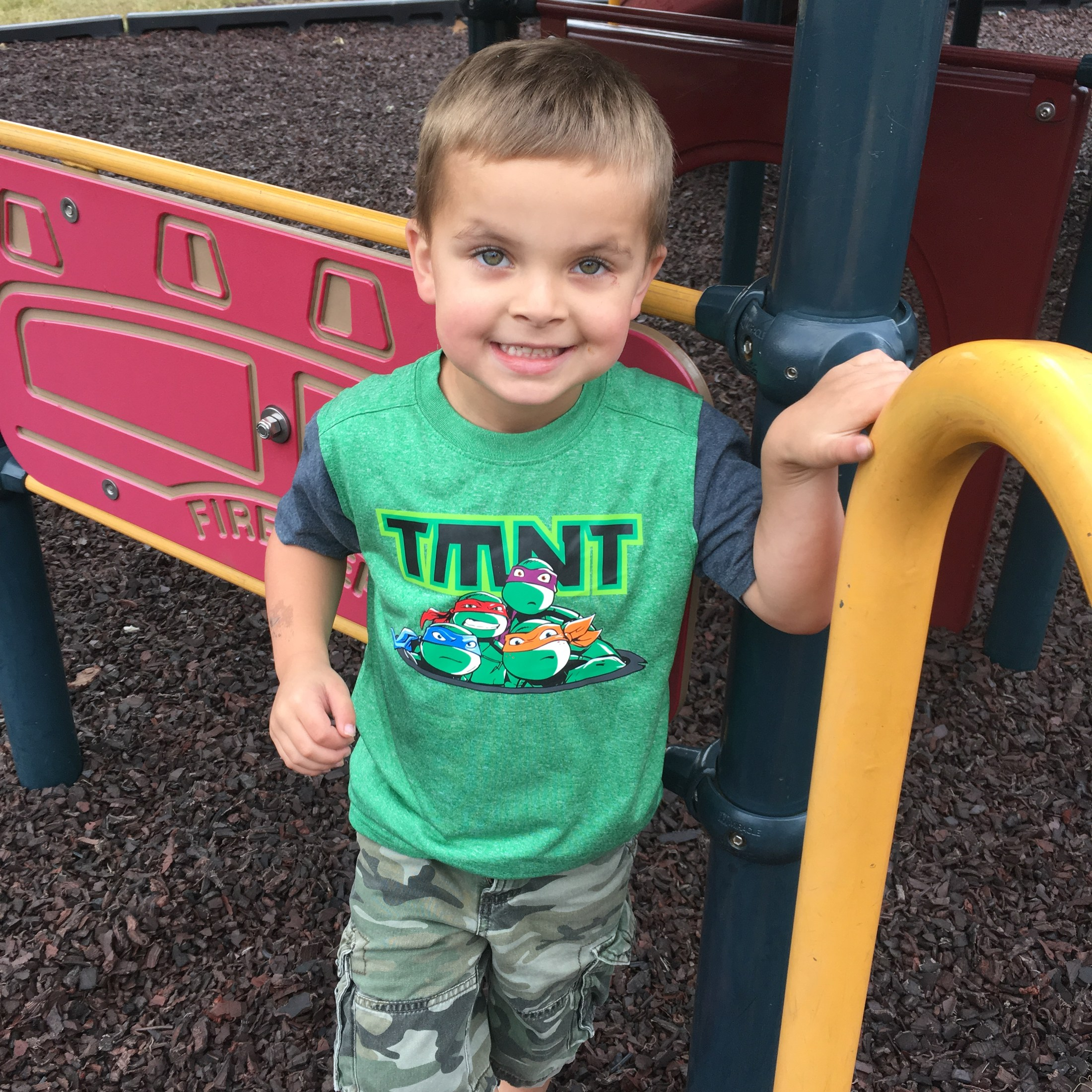 student in TMNT shirt on playground