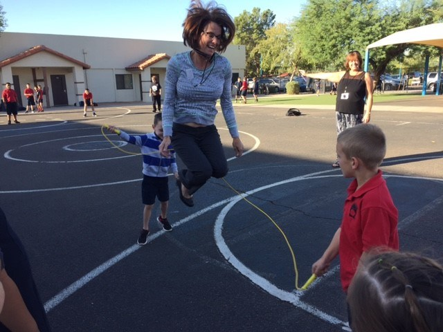 The principal jumping rope with two students on the playground.
