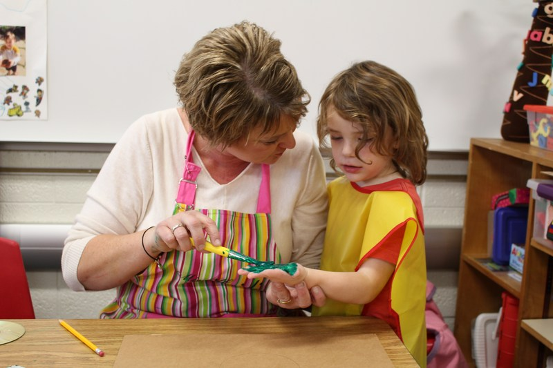 preschool teacher with apron and paint brush puts green paint on hand of preschooler with yellow bib on