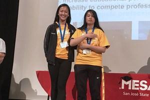students standing receiving award