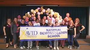 AVID team and AVID students holding National Demonstration banner