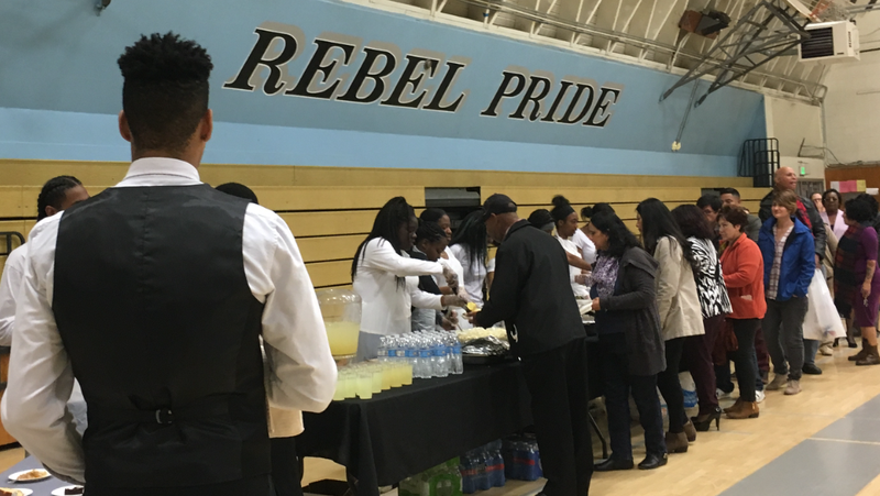 Students serving the long lines at the annual luncheon.