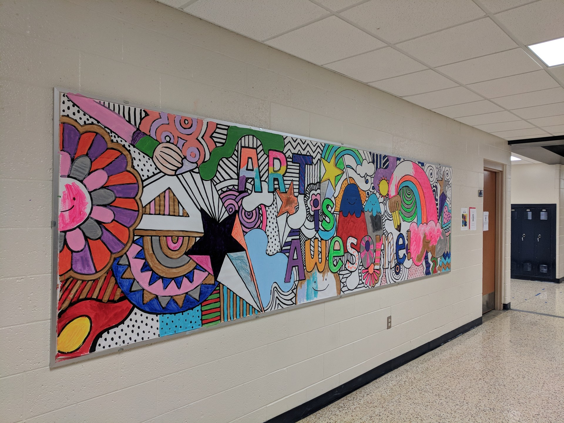 Painting is almost complete on the 'Art is Awesome' picture outside the art room.