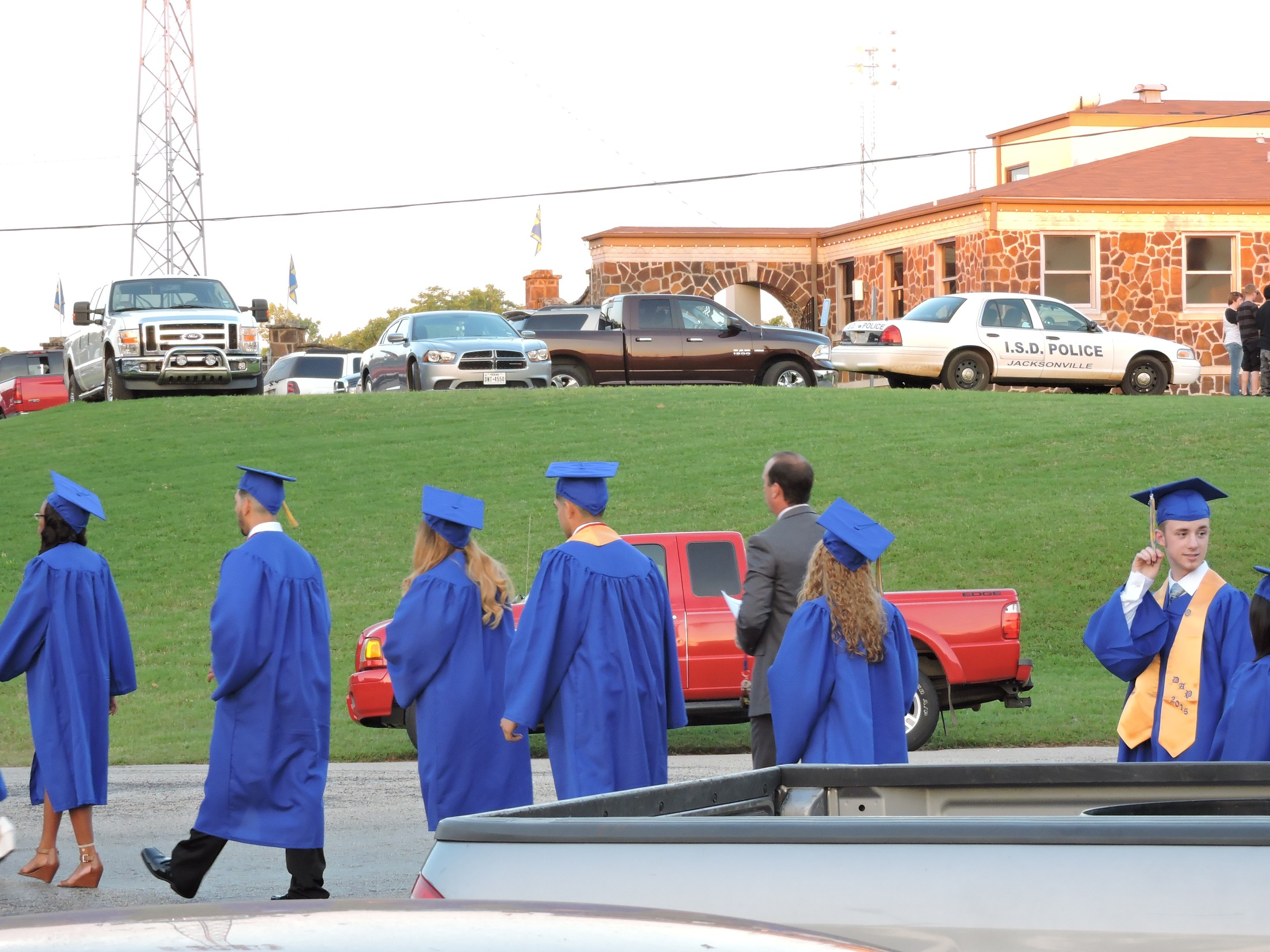 graduates walking to tomato bowl from Norman Center