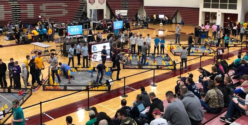 students play with robots in a gym