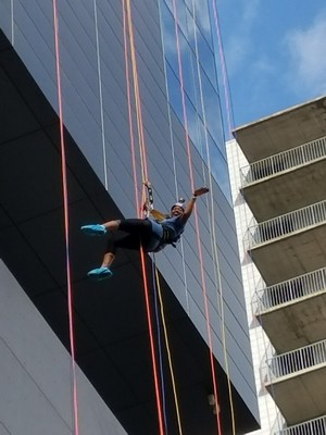 PCE Instructional Coach Ryane Gaston rappelling down the W Hotel.=