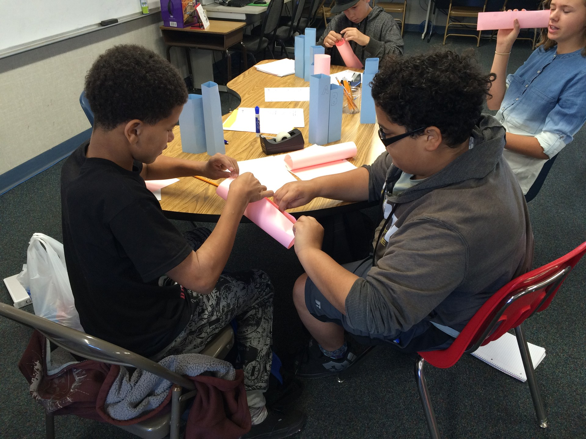 Students helping each other with math project.