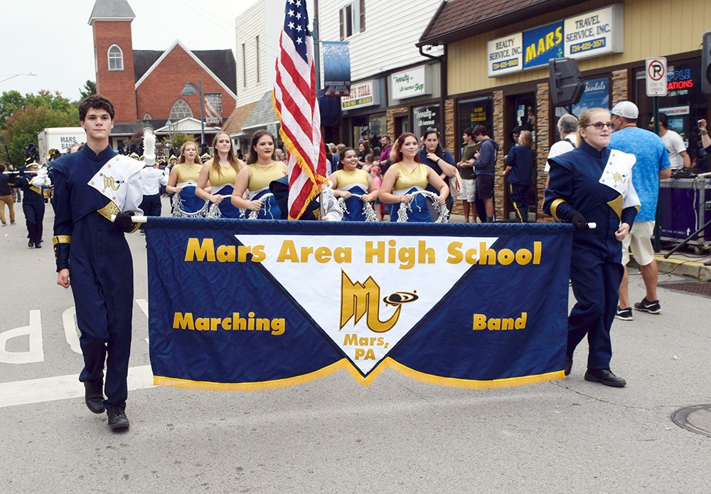 students leading band down center of street