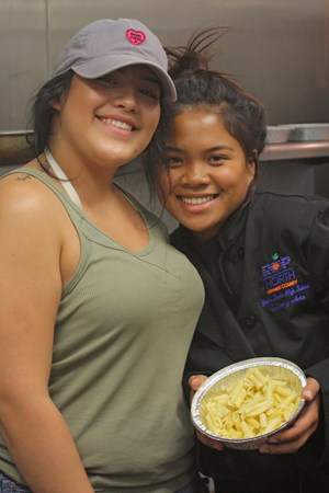two culinary arts students posing with food