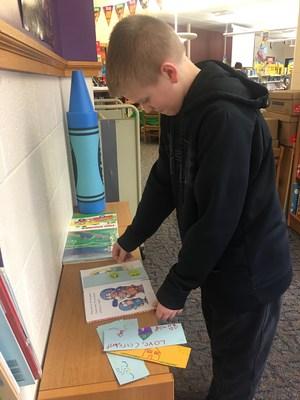 Colin puts a bookmark in a book.