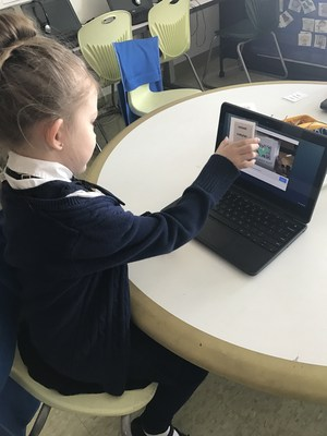 A Torres kindergarten student uses a badge with a QR code to log on to her computer.