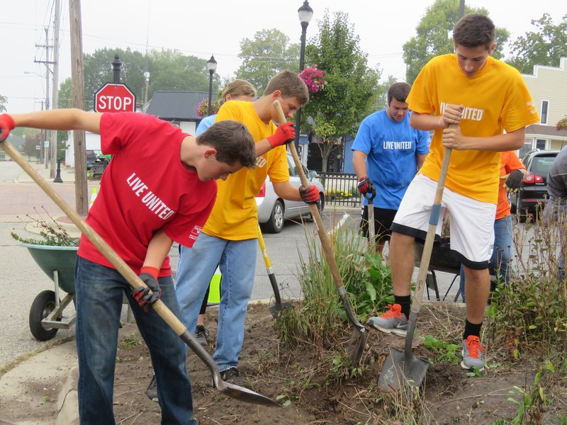 TKHS Student Council members clean up flower beds at the Thornapple Township Hall during the Day of Caring.