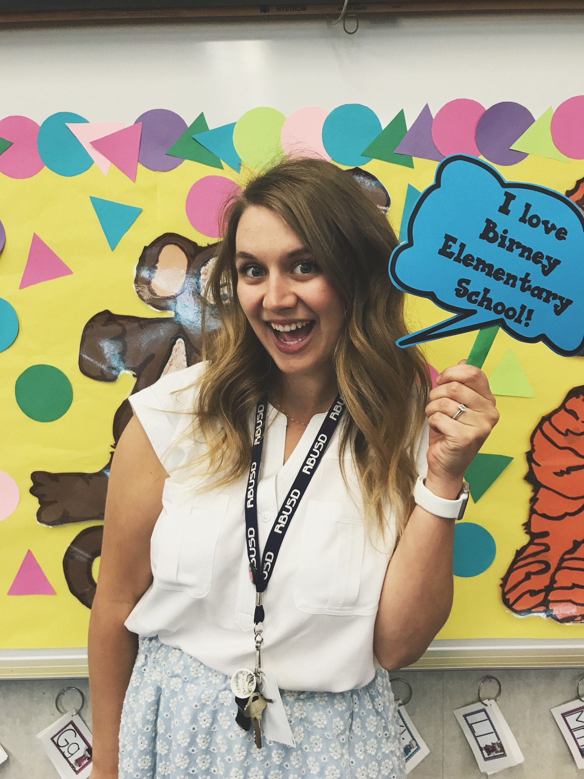 Marissa Roberts holding a sign that says 'I love Birney Elementary School!'
