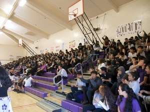 Several students sitting in bleachers in the school gym