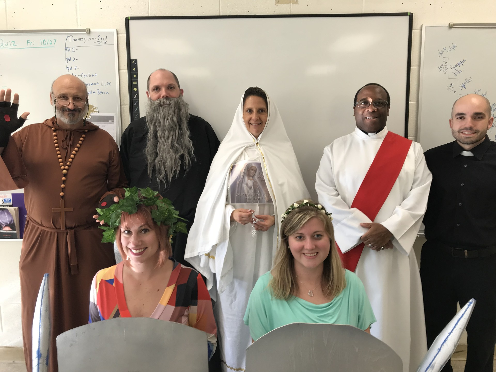 Theology staff posing in religious costumes for Halloween