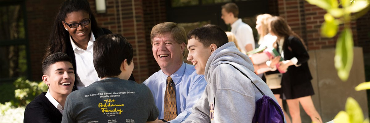 Principal Tim Plocinik engages with students on a sunny day