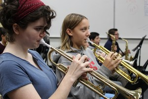 Band members play brass instruments.