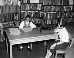 Two students in the library listen to a record on a Talking book machine.
