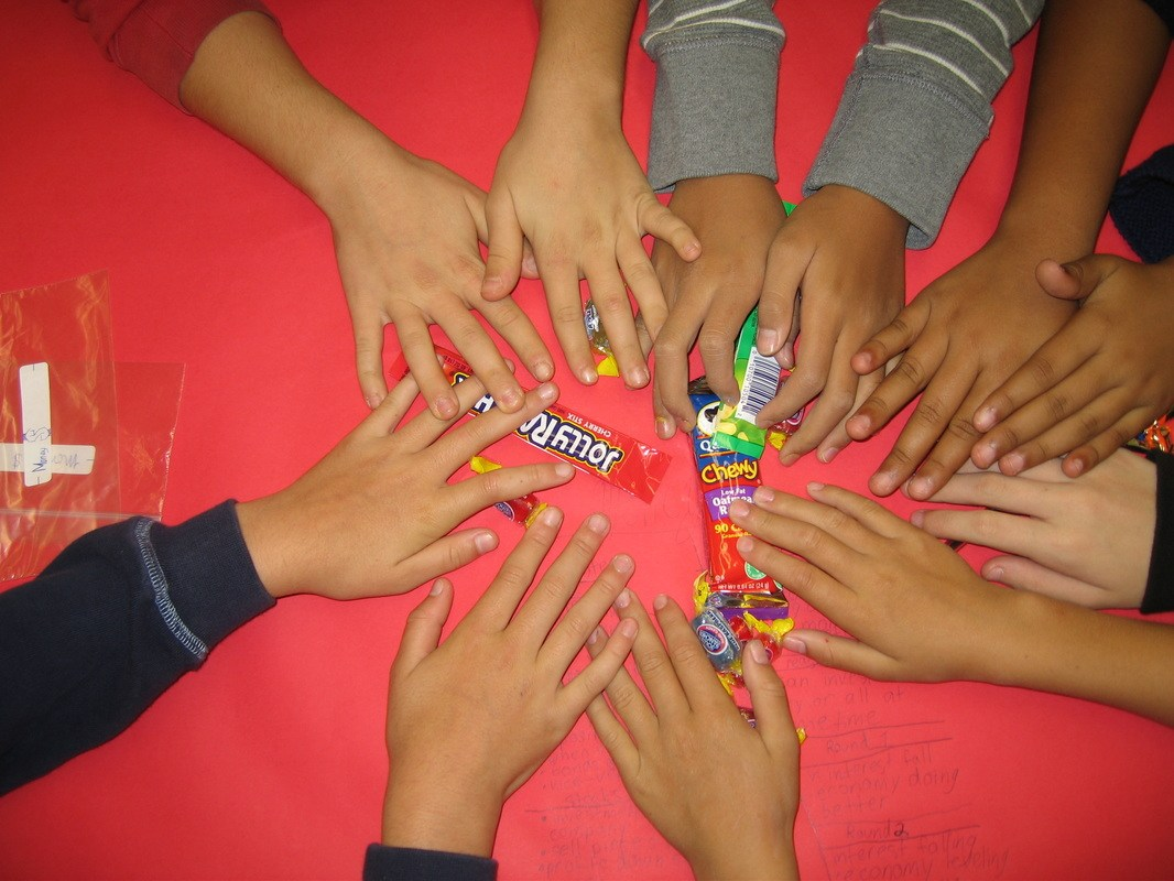 students hands grab assorted candy