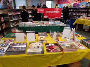 books on display on a table with yellow table cloth