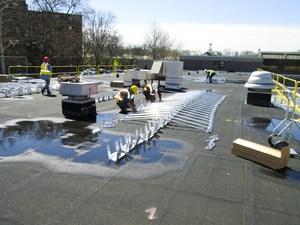 Workers on Frampton roof installing solar panel brackets