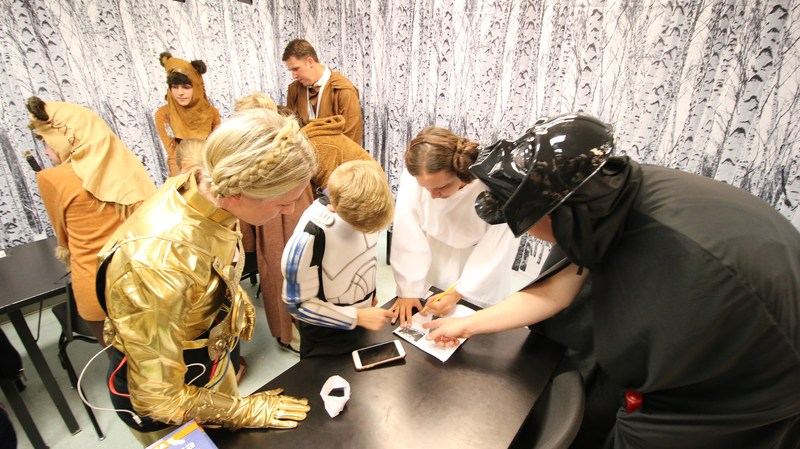 A family dressed in Star Wars costumes solving a puzzle