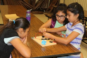 Three freeman students work together to build a circuit