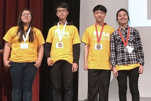 students on stage with medals