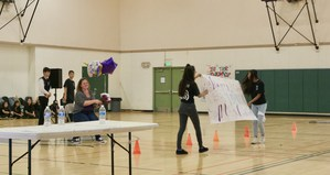 Two students hold a paper sign in the gym with the principal and other students seated in the background