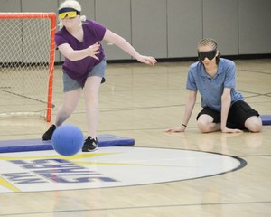 Girl camper tossing the goalball across the court
