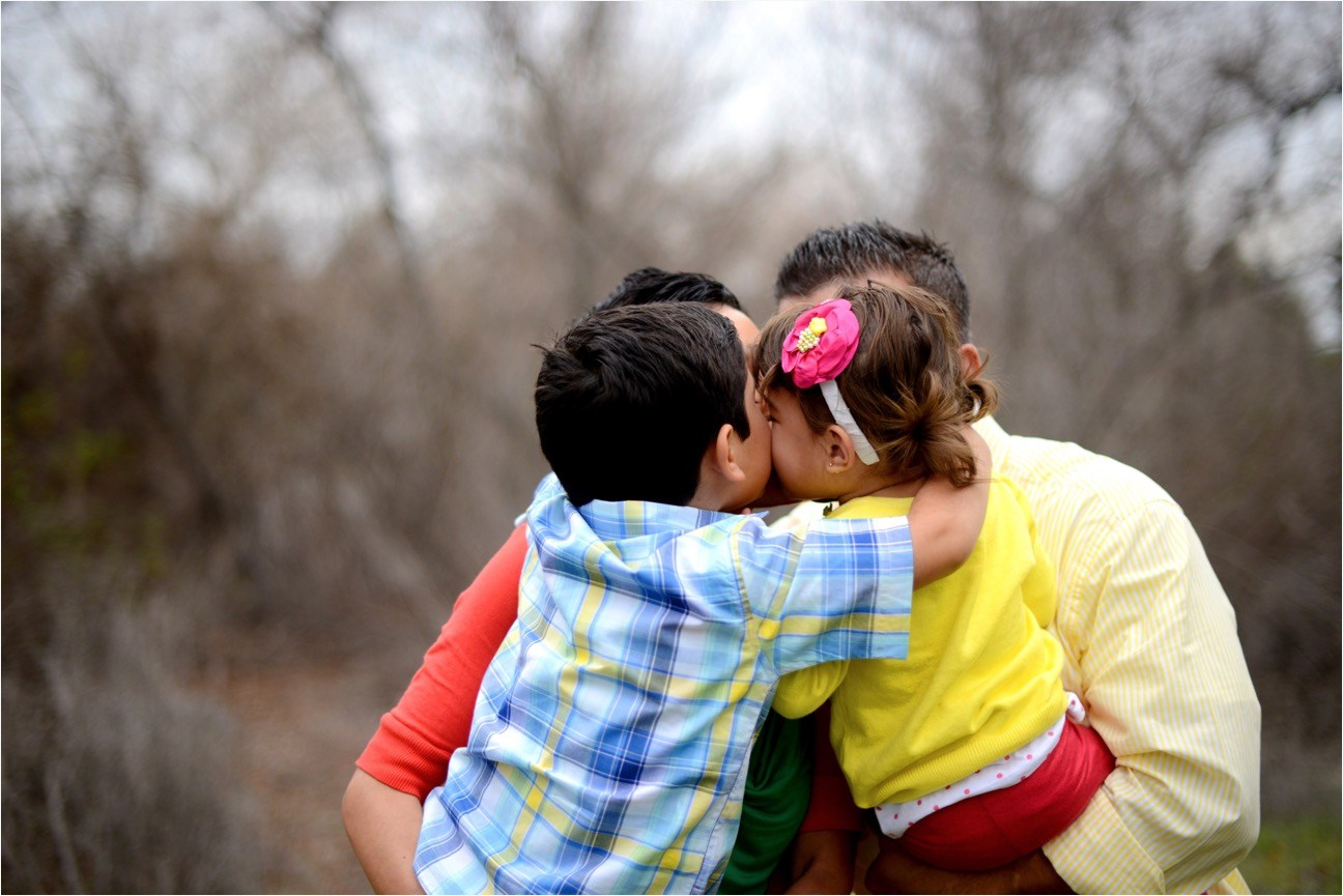 Image of children hugging in parents arms.