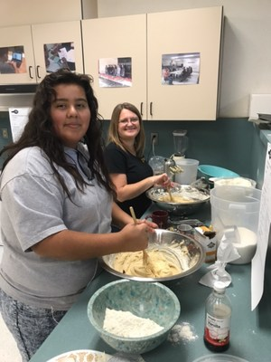 teacher and student mixing cookie dough