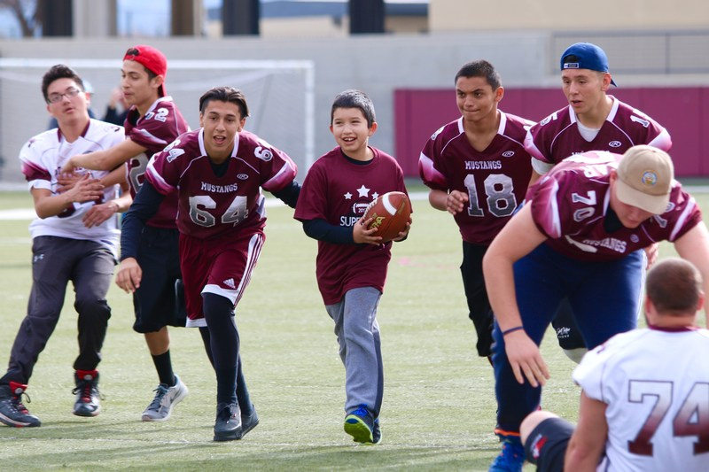 Sixth grade student running with the football with West Valley football players running along beside him.