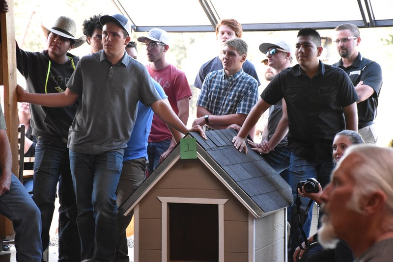Students in the Building Trades 1 class wait in anticipation for their first dog house to go on the auction block.