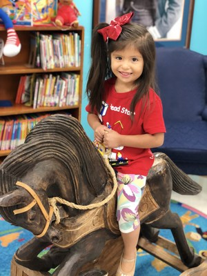Head Start student on wooden horse.
