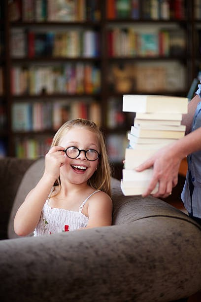 Smiling girl with round glasses looking over her shoulder at a stack of books