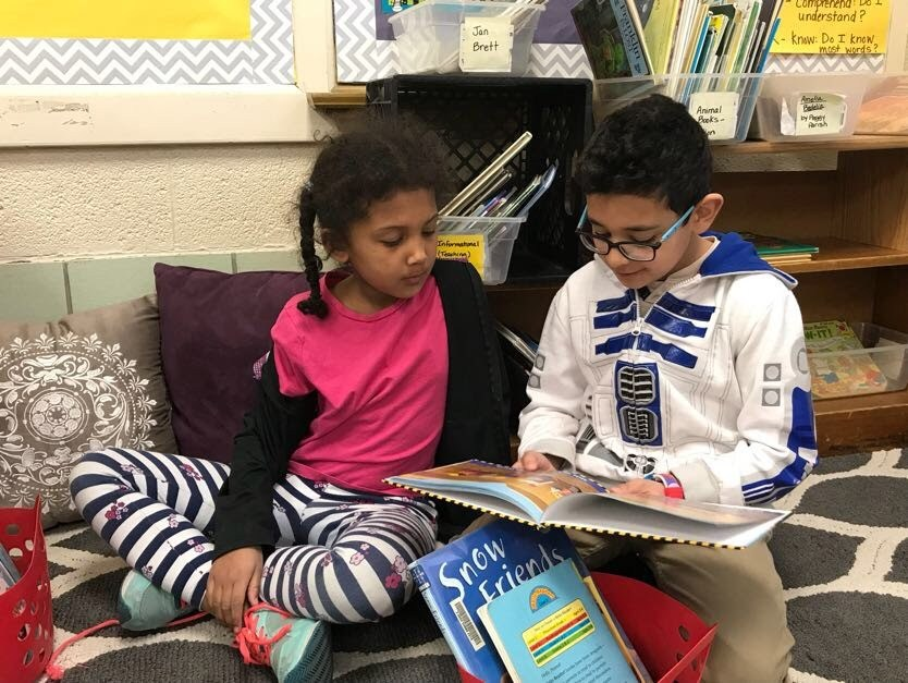 Students reading to each other.