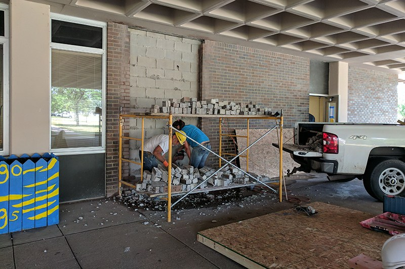 Workers take out bricks at Washington Street Elementary to create a new door for visitors.