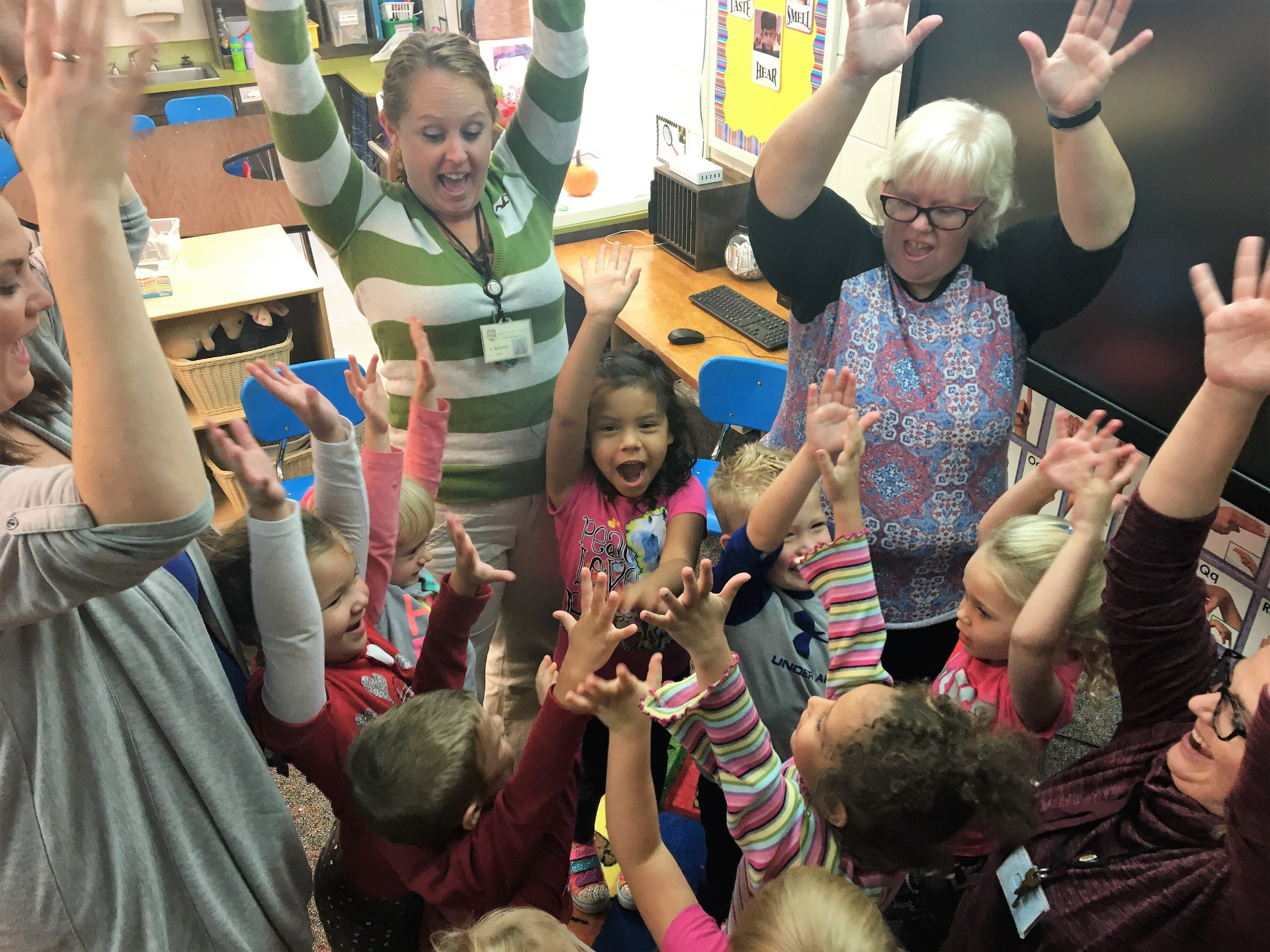 A group of students surrounding each other with their hands in the air.