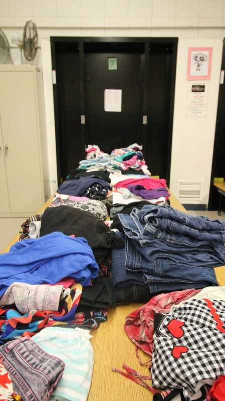 Clothes stacked on table.